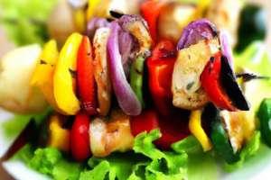 brochettes-de-poulet-avec-des-oignons-sur-le-dessus-d-39-une-salade_1220-567