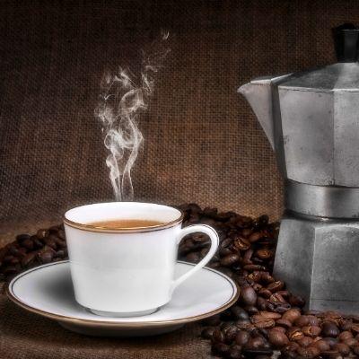 Tasse à café fumante et percolateur